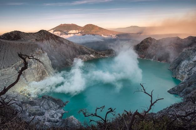 Кратер действующего вулкана с бирюзовым озером и серным дымом по утрам