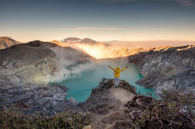 Человек, стоящий на гребне кратера на рассвете