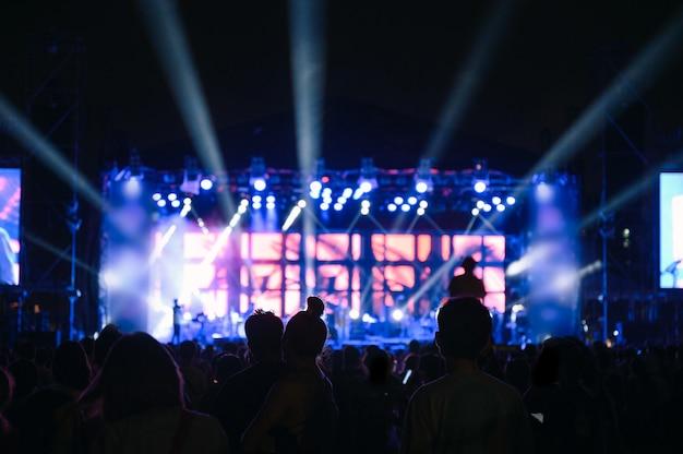 シルエットの若者の観客は夜のコンサートを見ています