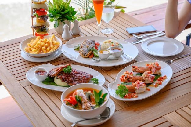 さまざまな料理、ローストポークリブ、ビーフステーキ、シーフード、ダイニングテーブルのスパイシーなスープ