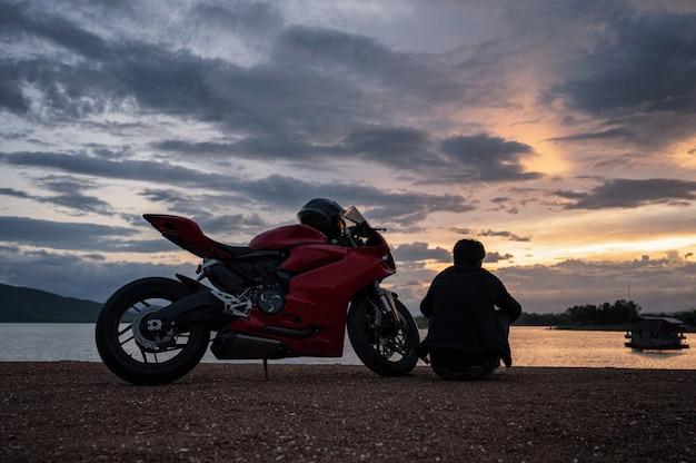 夕暮れ時の観光とスポーツの大きな自転車の側に座っている若いバイカー