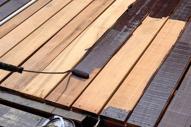木製の床にペイントローラーでペイントする労働者