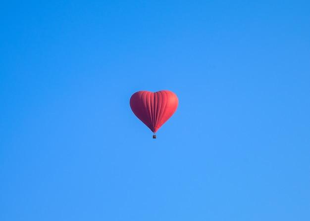 青い空を飛んでいるカラフルな熱気ハート形風船