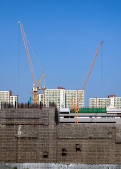 黄色いクレーンと足場の建設現場の建物