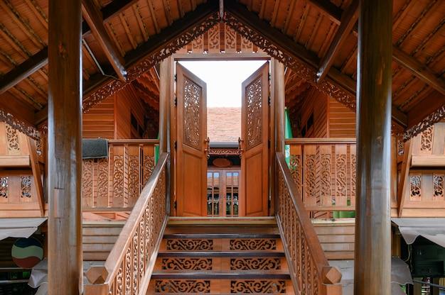 彫刻のドアの開口部を持つ古典的なアジアの木造住宅