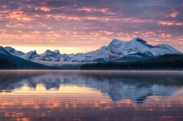 ジャスパー国立公園での朝のマリーン湖とカラフルな空の霧の反射とカナダのロッキー山脈
