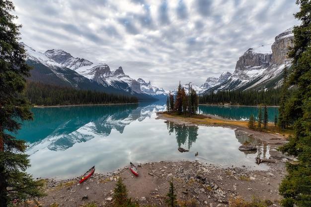 Каноэ на якоре с отражением канадских скалистых гор на озере малинье на острове спирит в национальном парке джаспер