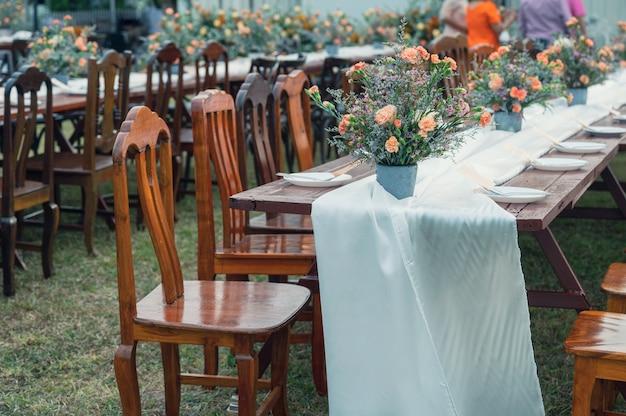 Деревенский стиль свадьбы, деревянный обеденный стол с цветами и посудой