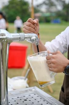 Бармен наливает разливное пиво из ручки крана машины