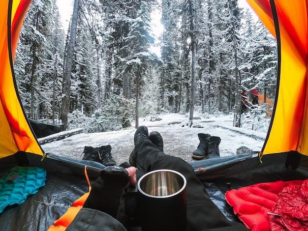 松の森の雪の上のテントの中でカップを持っている手でキャンプ旅行者