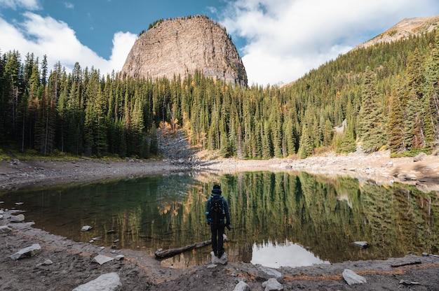 バンフ国立公園のレイクルイーズの秋の森のミラー湖に立っている男性カメラマン