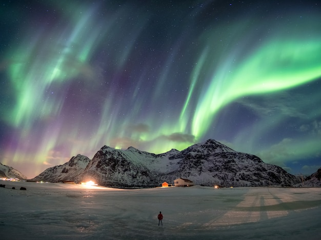 男が立っている雪山の上の素晴らしいオーロラのボレアリス