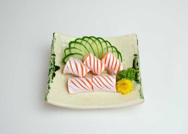 Нарезанный сырой лосось сашими с огурцом на тарелке