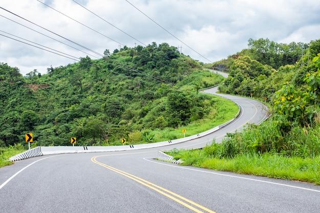 アスファルト道路が丘の上に湾曲