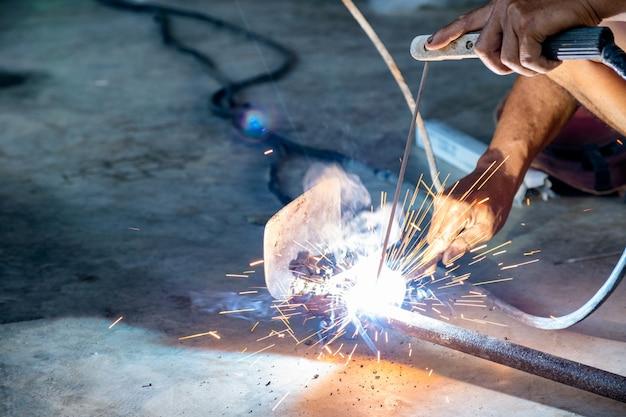 溶接機を使用して産業労働者はスペードツールを溶接しています