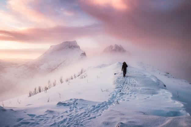吹雪の中で雪のピークの尾根の上の雪の足跡を歩く男登山家