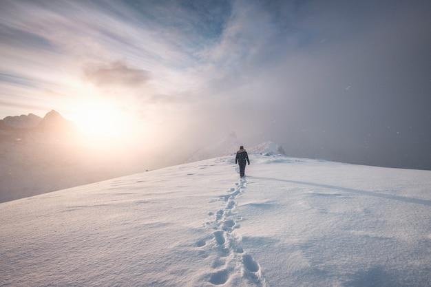 山の頂上に雪の足跡を歩く男登山家