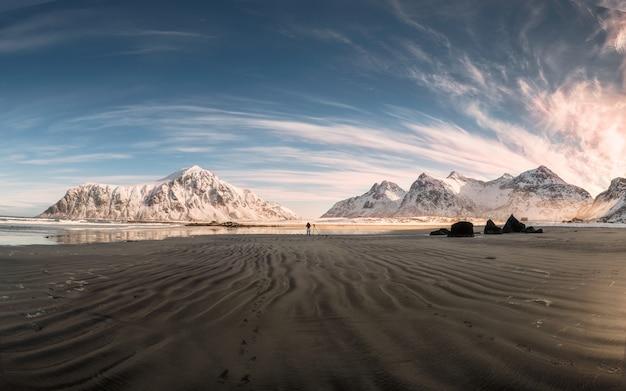 スキャグサンデンビーチで海岸線に砂の畝と雪の山脈のパノラマ