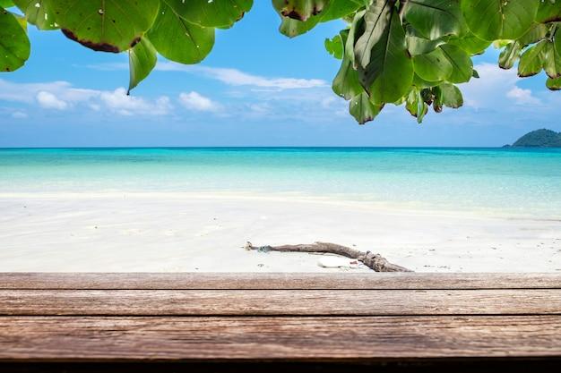 海のビーチのカラフルな白い砂の上の木のテーブルトップ