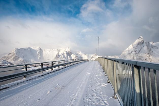雪に覆われた山と北極海に架かる橋