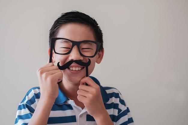 Портрет смешного смешного азиатского мальчика, весело с поддельными усами