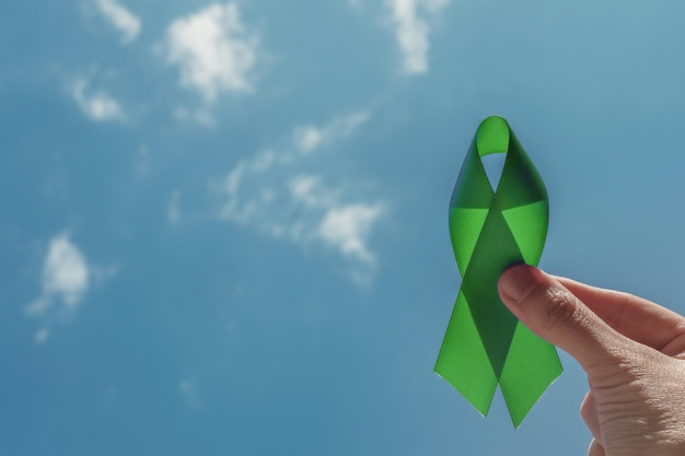 Рука с зеленой лентой над голубым небом