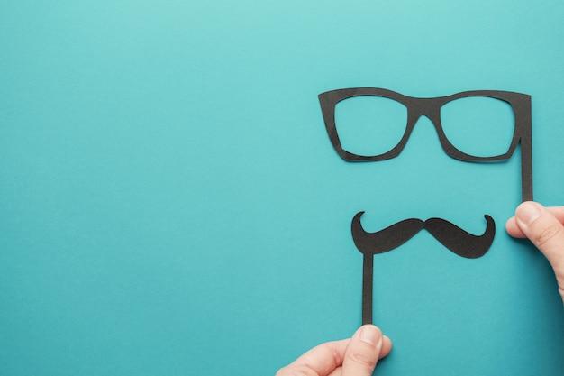 Руки держат бумажные усы и очки