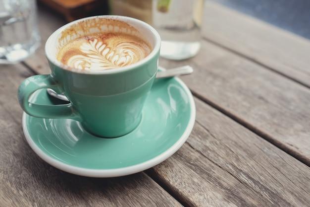 木製のテーブルにコーヒーカフェラテアートのカップ