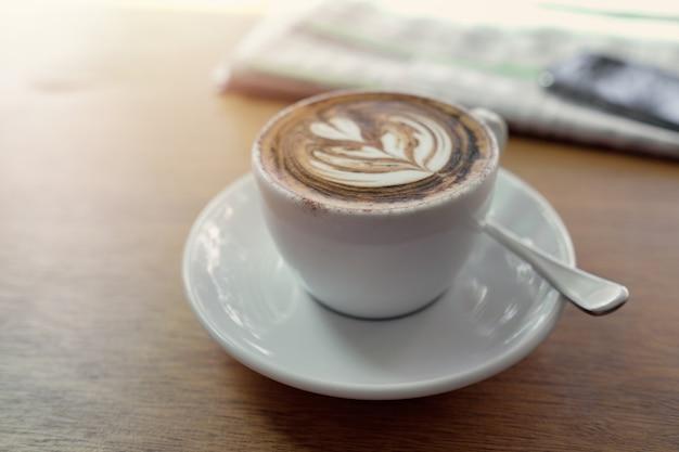 新聞とカプチーノコーヒーアートのカップ