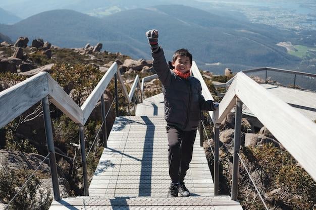 Азиатский подросток мальчик смешанной расы, стоя с поднятой рукой на вершине горы