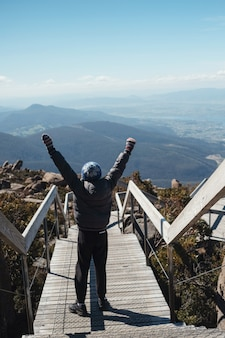 Мальчик-подросток стоит с поднятой рукой на вершине горы