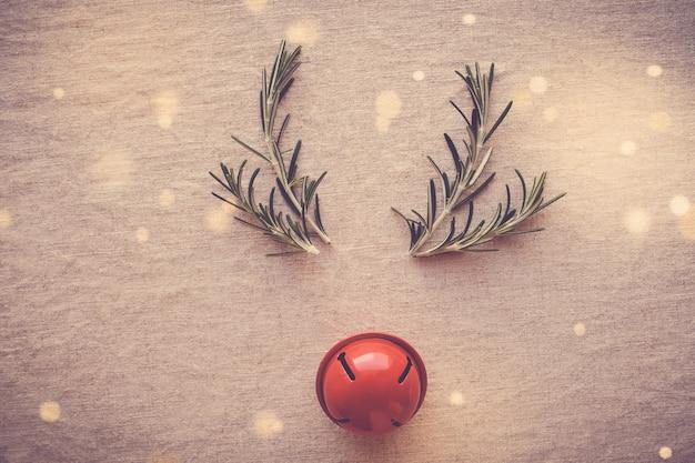 ローズマリーと赤い装飾ベルで作られた最小限の赤い鼻のトナカイ