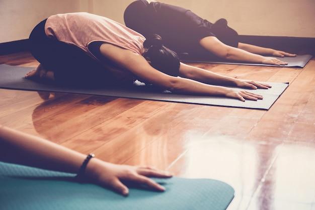 Группа молодых здоровых азиатских женщин практикующих урок йоги