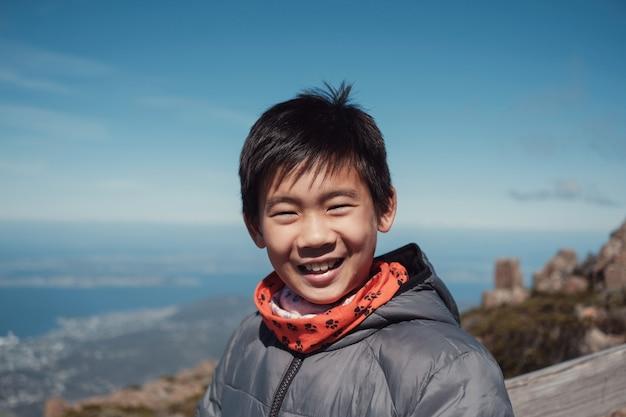 Счастливый и уверенный подросток смешанной расы азиатский мальчик улыбается на горы
