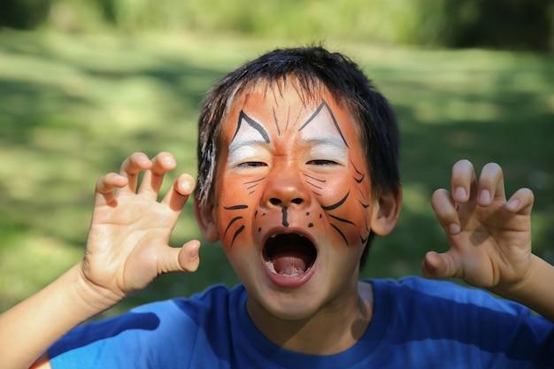 虎のように面白い顔の絵を描く若い少年
