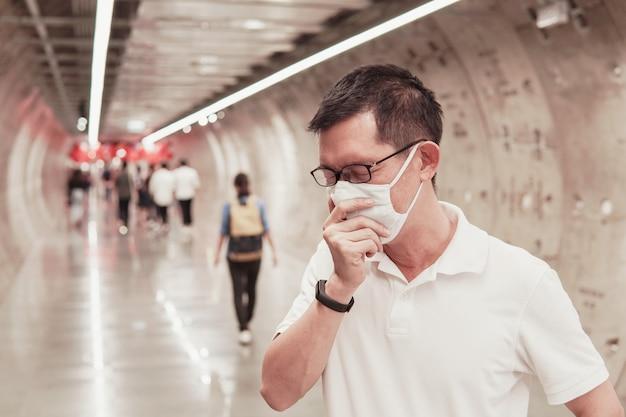 Азиатский мужчина средних лет в очках и медицинской маске, чихании и кашле, вспышке коронавируса в ухане, загрязнении воздуха и концепции здоровья