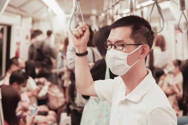 Азиатский мужчина средних лет в очках и медицинская маска на общественном поезде, вспышка коронавируса в ухане, загрязнение воздуха и концепция здоровья