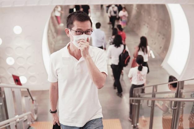 Азиатский мужчина средних лет в очках и медицинской маске, кашле и чихании, вспышке коронавируса в ухане, загрязнении воздуха и концепции здоровья
