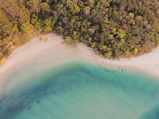 美しいターコイズブルーの海、ビーチ、木の森の散歩、ドローンからトップビューの空撮