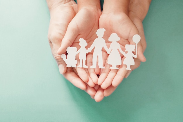 紙の家族の切り抜き、家族の家、養子縁組、里親ケアを保持している大人と子供の手。