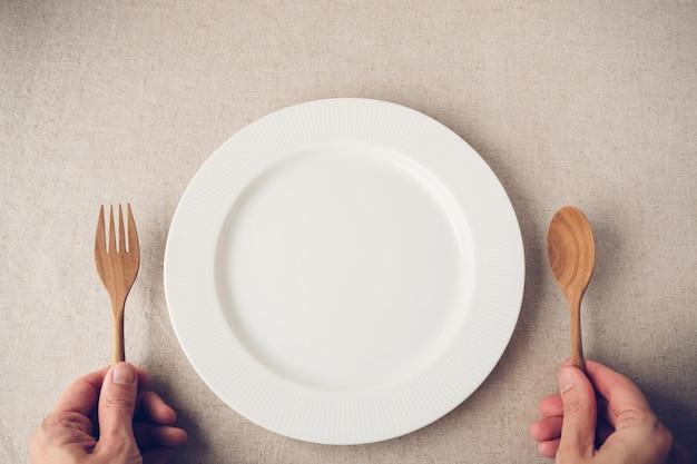 白いプレートにスプーンとフォーク、断続的な断食の概念、減量ダイエット