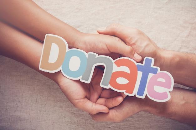 寄付という言葉、寄付、慈善の概念を保持している大人と子供の手
