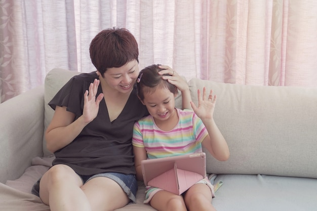 若いアジアの女の子と彼女の母親は、自宅のラップトップでフェイスタイムビデオ通話を行い、ズーム学習オンラインアプリを使用して、社会的距離、分離、ホームスクーリング教育、リモートコンセプトを学習