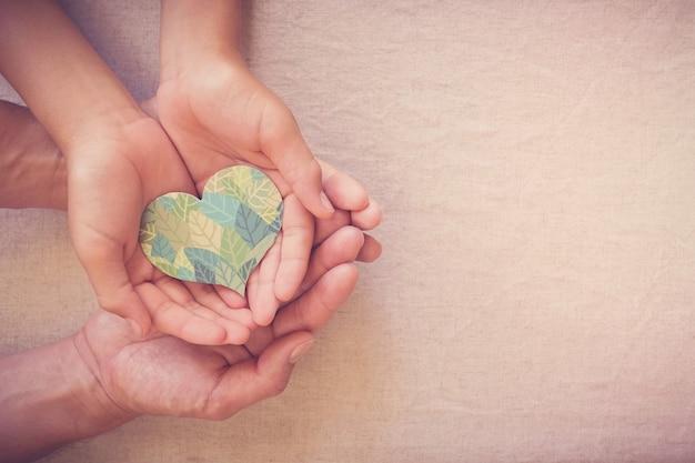Руки держат форму сердца листьев, социальную ответственность ксо, экологически устойчивую жизнь, веган, день окружающей среды мира, день земли