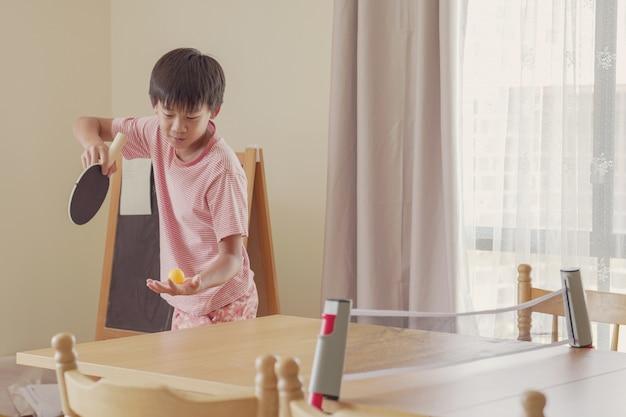 健康的な混合アジアプレティーンの少年が自宅のダイニングテーブルで卓球をプレイ、トゥイーン運動、子供のフィットネス、健康を維持し、社会的距離、分離の概念の中にフィット