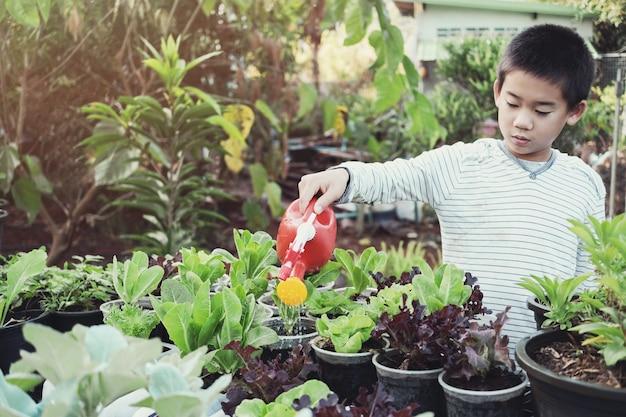 Азиатские мальчики поливают растения в повторном использовании старых пластиковых контейнеров