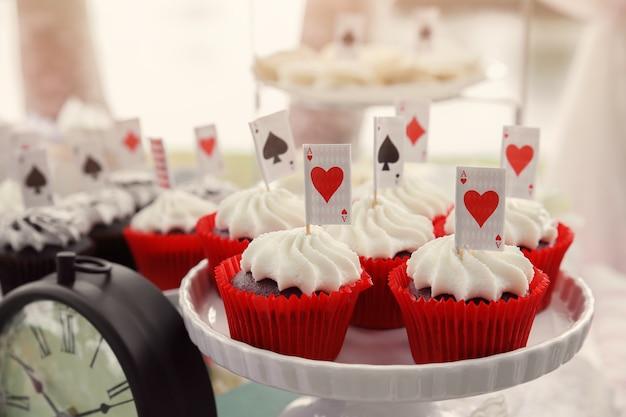 カードトッパー付きの赤いビロードカップケーキ、ワンダーランドティーパーティーのアリス