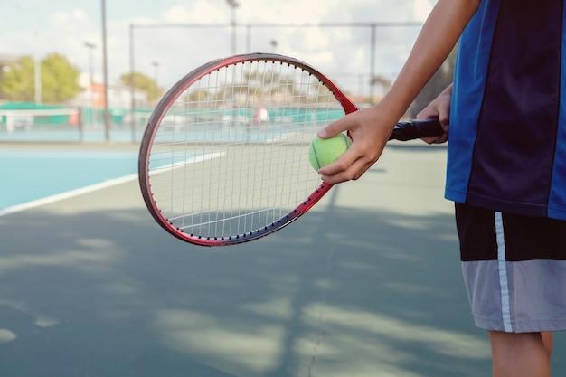 屋外の青いコートに若い男の子テニスプレーヤー