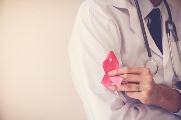Доктор, держащий розовую ленту, осведомленность о раке молочной железы, октябрьская розовая концепция