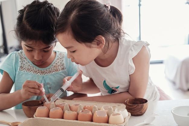 子供たちは再利用卵殻に苗を植え、モンテッソーリホームスクールの教育